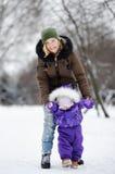 Mujer joven con su niña pequeña en el parque del invierno Imágenes de archivo libres de regalías
