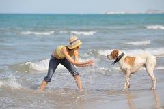 Mujer joven con su perro en la playa Foto de archivo