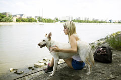 Mujer joven con su perro por un río Fotografía de archivo