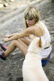Mujer joven con su perro por un río Fotos de archivo libres de regalías