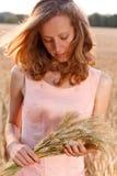 Mujer joven con trigo maduro de los oídos en las manos Imagen de archivo