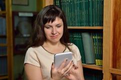 Mujer joven con un artilugio en la biblioteca Foto de archivo libre de regalías