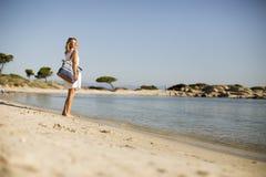 Mujer joven con un bolso que se coloca en la playa fotos de archivo