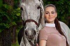Mujer joven con un caballo blanco Imagen de archivo