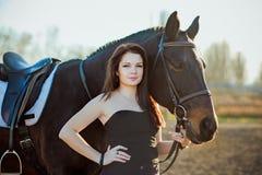 Mujer joven con un caballo en la naturaleza Imagen de archivo