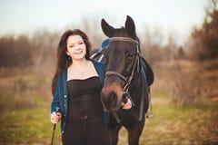 Mujer joven con un caballo en la naturaleza Foto de archivo