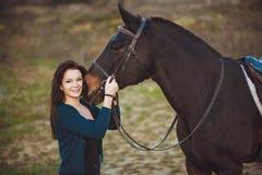 Mujer joven con un caballo en la naturaleza Fotos de archivo