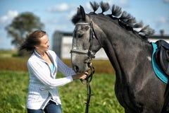 Mujer joven con un caballo gris Imagen de archivo