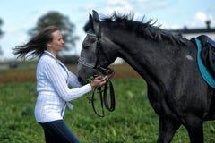 Mujer joven con un caballo gris Imagenes de archivo