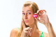 Mujer joven con un condón imagenes de archivo