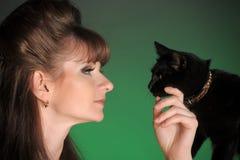 Mujer joven con un gato negro Fotos de archivo