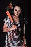 Mujer joven con un hacha sangrienta grande Foto de archivo libre de regalías