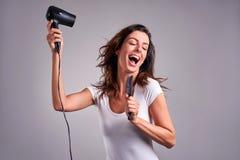 Mujer joven con un hairdryer imagenes de archivo