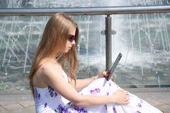 Mujer joven con un libro digital Imagenes de archivo