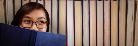 Mujer joven con un libro que parece derecho delante de los libros Imágenes de archivo libres de regalías