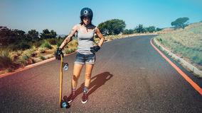 Mujer joven con un longboard en la carretera del campo Fotografía de archivo