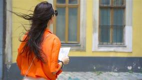 Mujer joven con un mapa de la ciudad en ciudad Muchacha turística del viaje con el mapa en Viena al aire libre durante días de fi almacen de video