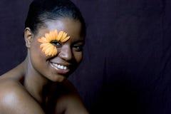 Mujer joven con un ojo de la margarita del Gerbera Fotos de archivo
