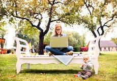 Mujer joven con un ordenador portátil que estudia al aire libre Fotografía de archivo