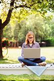 Mujer joven con un ordenador portátil que estudia al aire libre Imagenes de archivo