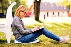 Mujer joven con un ordenador portátil que estudia al aire libre Foto de archivo libre de regalías