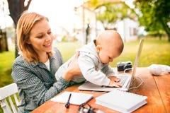 Mujer joven con un ordenador portátil que estudia al aire libre Fotografía de archivo libre de regalías