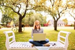 Mujer joven con un ordenador portátil que estudia al aire libre Fotos de archivo