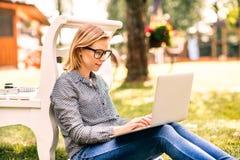 Mujer joven con un ordenador portátil que estudia al aire libre Fotos de archivo libres de regalías