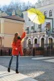 Mujer joven con un paraguas amarillo que salta al aire libre Imagen de archivo