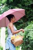Mujer joven con un paraguas y sostener una cesta Fotografía de archivo libre de regalías