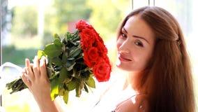 Mujer joven con un ramo de rosas rojas cerca de una ventana abierta Una muchacha hermosa disfruta del aroma de flores almacen de metraje de vídeo