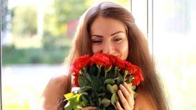Mujer joven con un ramo de rosas rojas cerca de una ventana abierta Una muchacha hermosa disfruta del aroma de flores metrajes