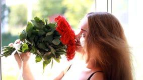 Mujer joven con un ramo de rosas rojas cerca de una ventana abierta Una muchacha hermosa disfruta del aroma de flores almacen de video