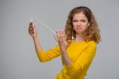 Mujer joven con un smartphone y auriculares con un wir enredado Fotos de archivo libres de regalías