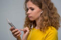Mujer joven con un smartphone y auriculares con un wir enredado Imagen de archivo libre de regalías