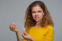 Mujer joven con un smartphone y auriculares con un wir enredado Imagen de archivo
