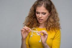 Mujer joven con un smartphone y auriculares con un wir enredado Imágenes de archivo libres de regalías