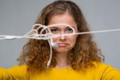 Mujer joven con un smartphone y auriculares con un wir enredado Foto de archivo