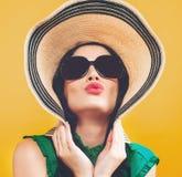 Mujer joven con un sombrero y las gafas de sol imagenes de archivo
