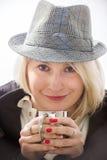 Mujer joven con un sombrero y una taza metálica Fotos de archivo