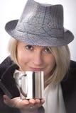 Mujer joven con un sombrero y una taza metálica Fotos de archivo libres de regalías