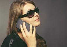 Mujer joven con un teléfono móvil Foto de archivo libre de regalías