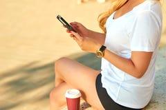 Mujer joven con un teléfono móvil en sus manos Fotos de archivo