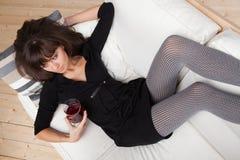 Mujer joven con un vidrio de vino rojo Foto de archivo