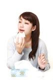 Mujer joven con una alergia que estornuda en tejido Imágenes de archivo libres de regalías