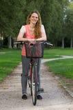 Mujer joven con una bici Fotografía de archivo libre de regalías