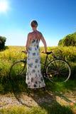 Mujer joven con una bicicleta Fotos de archivo
