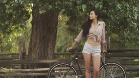 Mujer joven con una bicicleta al aire libre metrajes