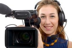 Mujer joven con una cámara de vídeo, en el fondo blanco Imagen de archivo