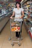 Mujer joven con una carretilla en un supermercado Imagen de archivo libre de regalías